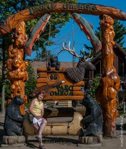 Crystine avec une vue globale de l'enseigne du parc devant le magasin général.